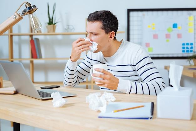 Ziekte op kantoor. zieke mannelijke persoon met beker in de linkerhand en neus afvegen tijdens het werken met de computer