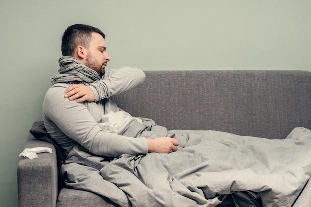 Ziekte. thuis juichen. een jonge man is ziek, wordt thuis behandeld. blaast haar neus in een servet, loopneus. infectie, epidemie, bacillus-drager.