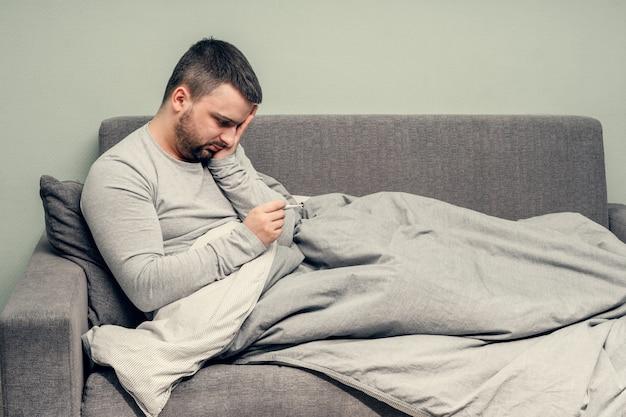 Ziekte. thuis juichen. een jonge man is ziek, wordt thuis behandeld. blaast haar neus in een servet, loopneus. lichaamstemperatuurmeting. infectie, epidemie, bacillus-drager. coronavirus