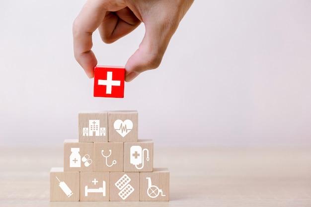 Ziektekostenverzekering concept, hand schikken hout blok stapelen met medische pictogram gezondheidszorg, voor de gezondheid