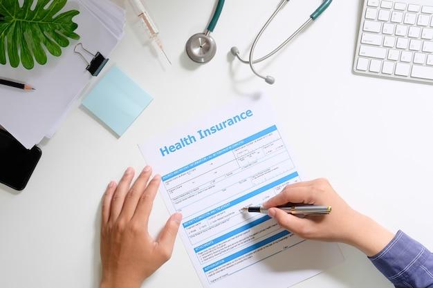 Ziektekostenverzekering concept, man teken en het lezen van ziekteverzekering met bovenaanzicht op bureau.