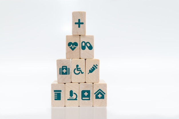 Ziektekostenverzekering concept. medische symbolen op houten blokken gestapeld in een piramide op witte achtergrond.