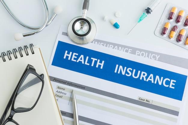 Ziektekostenverzekering formulier met stethoscoop in bovenaanzicht