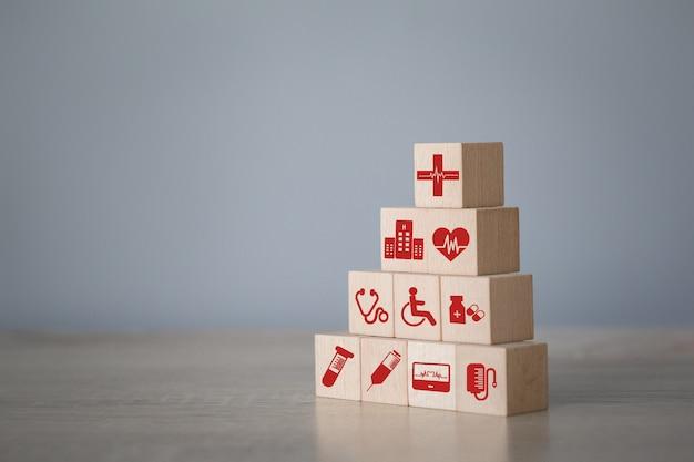 Ziektekostenverzekeringconcept, die houtsnede het stapelen met medische pictogramgezondheidszorg schikken.