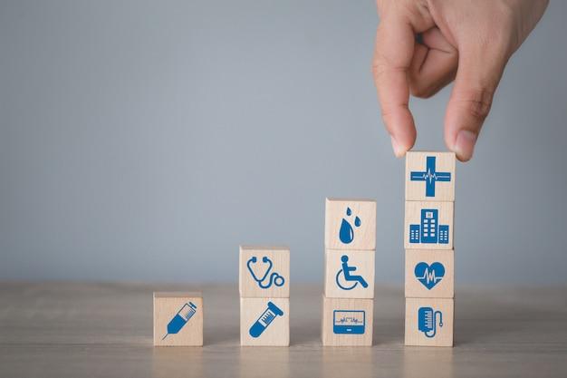 Ziektekostenverzekeringconcept, hand die houtsnede het stapelen met medische pictogramgezondheidszorg schikken.