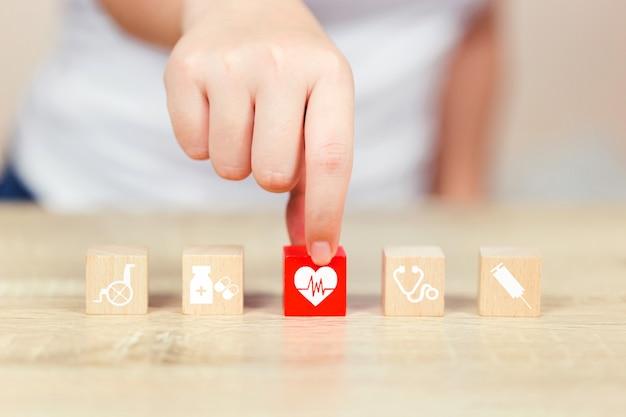 Ziektekostenverzekeringconcept, hand die houtsnedestapelen met medische pictogramgezondheidszorg schikken.