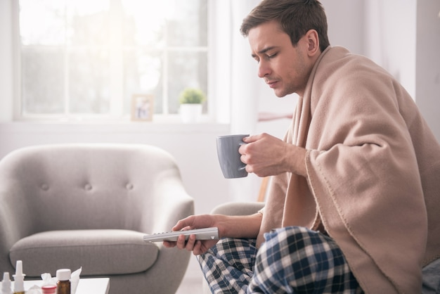 Ziekteverlof. trieste ongezellige man met thee terwijl hij bedekt is met plaid