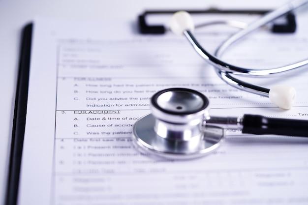 Ziekteverzekering ongeval claimformulier met stethoscoop