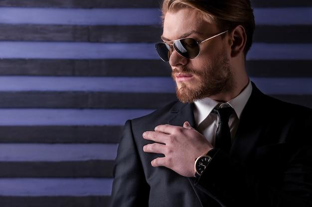 Ziet er altijd trendy uit. knappe jonge man in zonnebril en formalwear die zijn schouder met de hand aanraakt terwijl hij tegen een gestreepte achtergrond staat