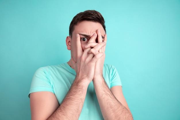 Ziet er bang uit. portret van de blanke jonge man geïsoleerd op blauwe muur. mooi mannelijk model in casual stijl, pastelkleuren. concept van menselijke emoties, gezichtsuitdrukking