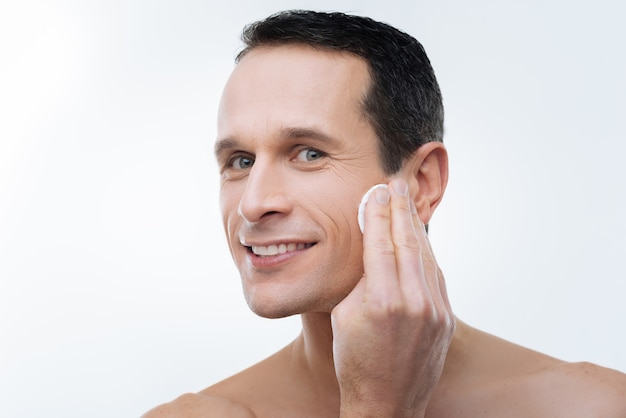 Ziet er goed uit. portret van een knappe man in verrukking met behulp van een wattenschijfje tijdens het schoonmaken van zijn huid