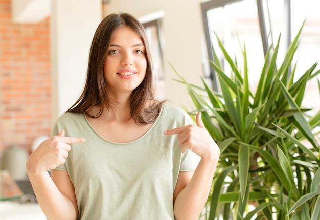 Ziet er trots, positief en casual uit en wijst met beide handen naar de borst