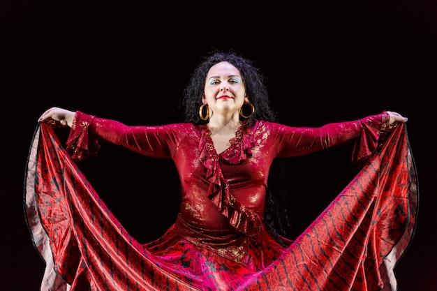 Zigeunervrouw met lang zwart haar danst in een rode jurk op een zwarte achtergrond. horizontale foto