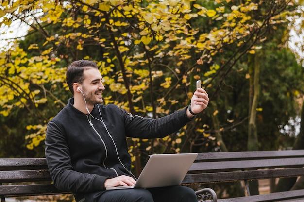 Zij beeld van een gelukkige kerel die een slimme telefoonzitting op een bank in een park gebruikt