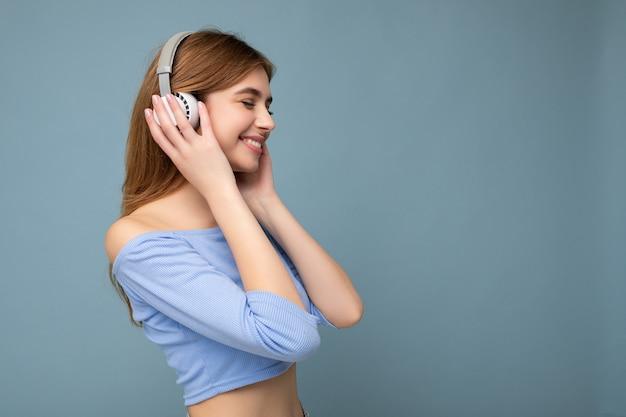 Zij-profielfoto van mooie positieve glimlachende jonge blonde vrouw die blauwe crop top draagt