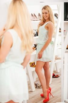 Zij zien er goed uit! volledige lengte van vrolijke jonge vrouw die nieuwe schoenen probeert en in de spiegel kijkt terwijl ze in de schoenenwinkel staat