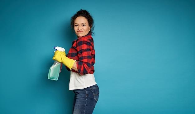 Zijaanzicht aan een gemengde rasvrouw die een wasmiddel schoonmakende nevel houdt en de camera bekijkt, die zich voordeed over blauw