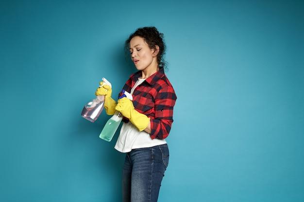 Zijaanzicht aan een mooie gemengde rasvrouw die een wasmiddel schoonmakende nevel houdt en over blauw danst