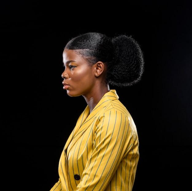 Zijaanzicht afrikaanse vrouw in gele jas