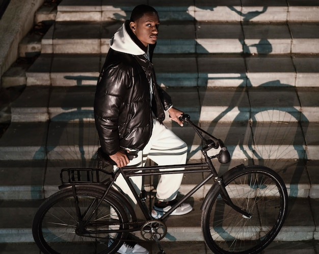 Zijaanzicht afro-amerikaanse fietser die de trap oploopt