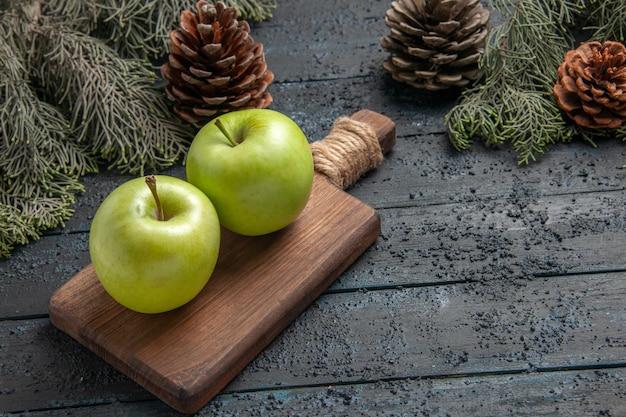 Zijaanzicht appels tussen takken twee smakelijke groene appels op snijplank tussen boomtakken met kegels with