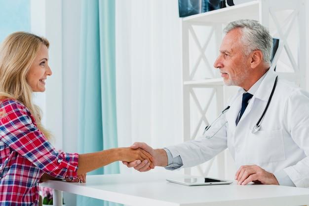Zijaanzicht arts die geduldige hand schudt