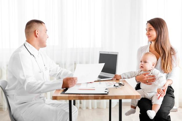 Zijaanzicht arts in gesprek met moeder van een baby