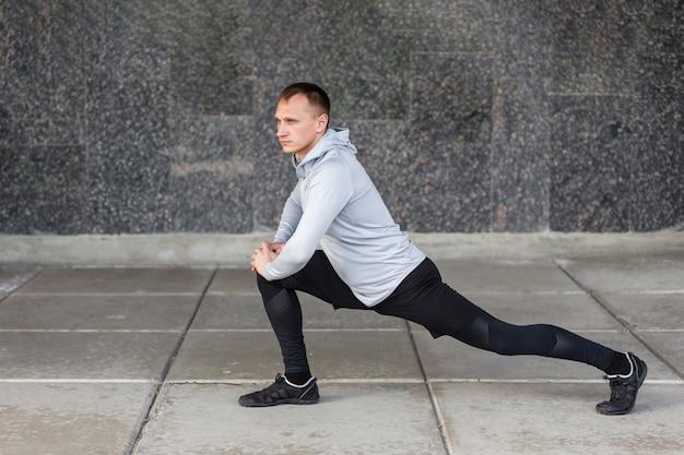 Zijaanzicht atletische man doet warming-up oefeningen