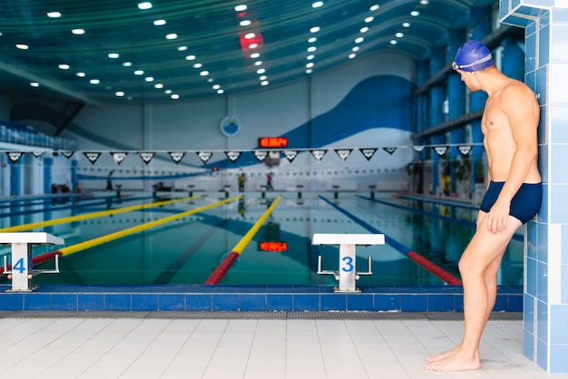 Zijaanzicht atletische man kijkt naar het zwembad