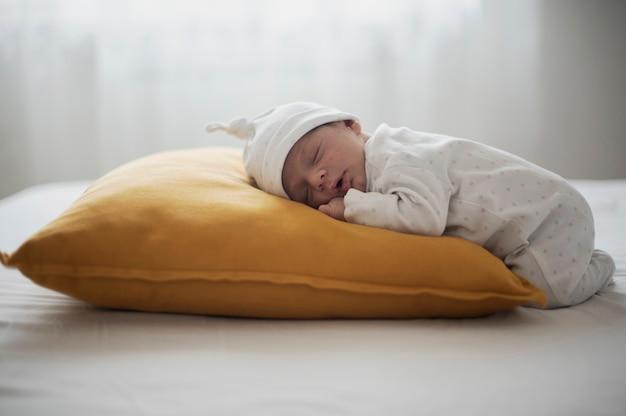 Zijaanzicht baby slaapt op een geel kussen