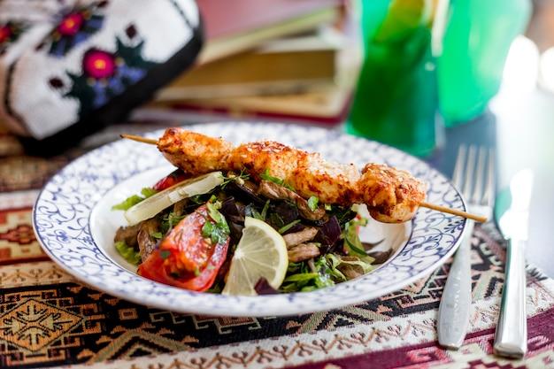 Zijaanzicht barbecue kip op een spies met groente salade en een schijfje citroen