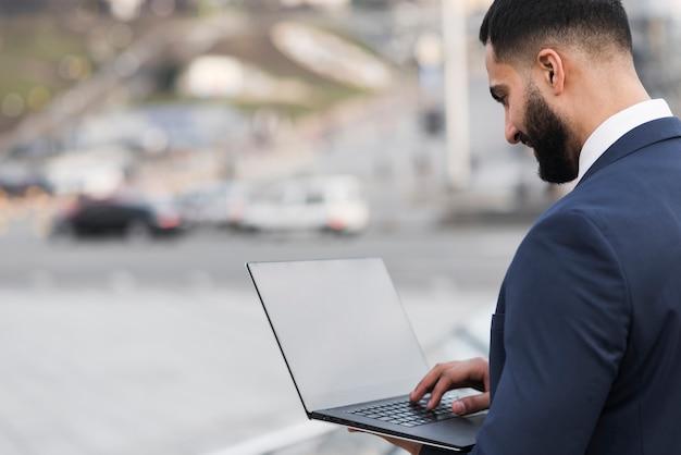Zijaanzicht bedrijfsmannetje met laptop