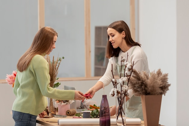 Zijaanzicht bedrijfsvrouwen die de bloemenwinkel schikken