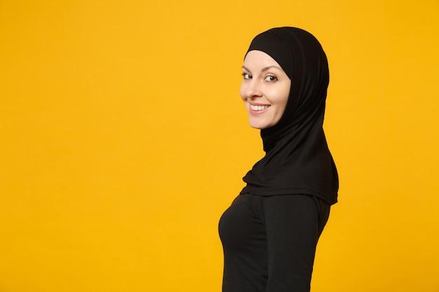 Zijaanzicht beeld van mooie jonge arabische moslimvrouw in hijab zwarte kleding poseren geïsoleerd op gele muur, portret. mensen religieuze islam levensstijl concept.