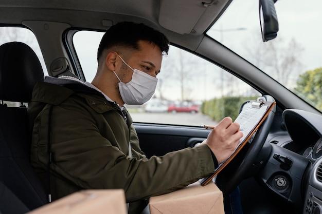 Zijaanzicht bezorger met masker in auto