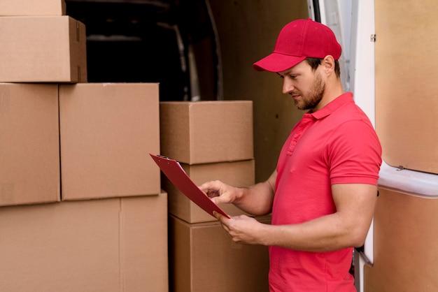 Zijaanzicht bezorger pakketten lijst controleren