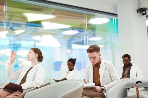 Zijaanzicht bij een groep jongeren die laboratoriumjassen dragen terwijl ze in het publiek zitten en luisteren naar een lezing over medicijnen op de universiteit of een coworkingcentrum, kopieer ruimte
