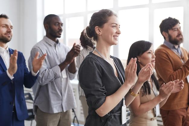 Zijaanzicht bij een multi-etnische groep zakenmensen die applaudisseren terwijl ze opstaan en glimlachen in het publiek op een zakelijke conferentie of seminar