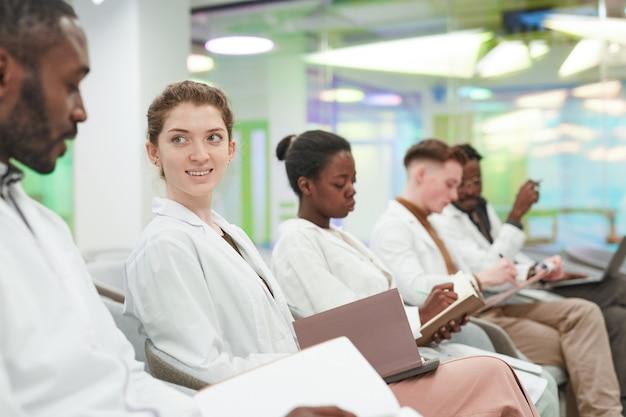 Zijaanzicht bij multi-etnische groep jongeren die laboratoriumjassen dragen terwijl ze in de rij in het publiek zitten en luisteren naar een lezing over medicijnen op de universiteit of een coworkingcentrum, kopieer ruimte