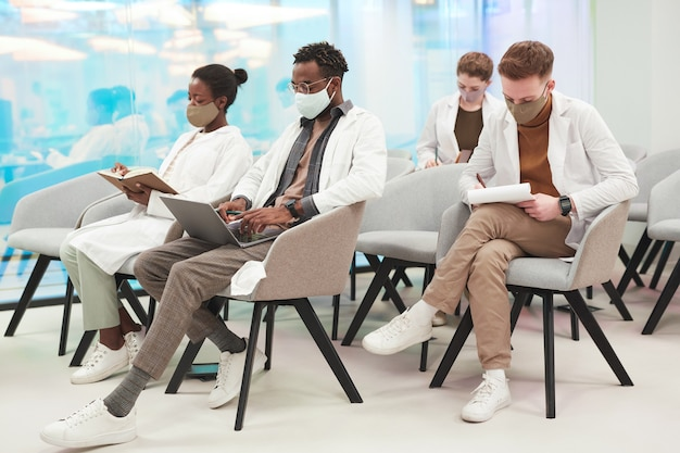 Zijaanzicht bij multi-etnische groep mensen die maskers en laboratoriumjassen dragen terwijl ze luisteren naar een lezing over medicijnen op de universiteit of een coworkingcentrum, kopieer ruimte