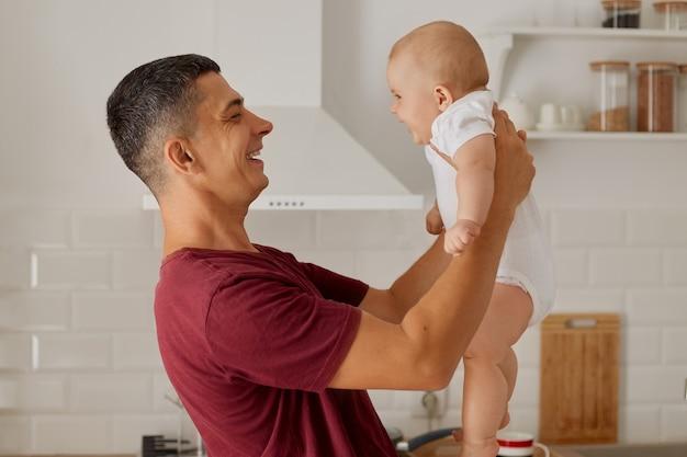 Zijaanzicht binnenportret van man vader in kastanjebruin t-shirt die zijn dochter of zoon in handen houdt terwijl hij in de keuken staat, gelukkig gezin, vaderschap, ouderschap.