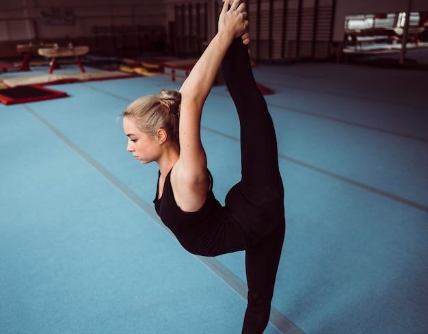 Zijaanzicht blonde jonge vrouw training voor olympische gymnastiek