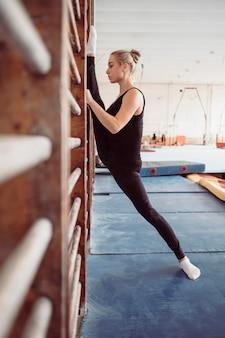 Zijaanzicht blonde vrouw trainen voor olympische gymnastiek