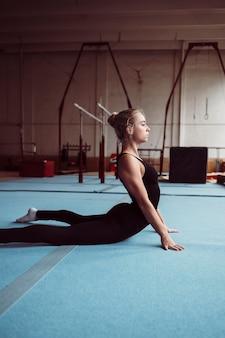 Zijaanzicht blonde vrouw training voor olympische gymnastiek