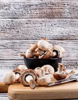 Zijaanzicht bruine en witte champignons in kom en op snijplank met mes op lichte houten tafel