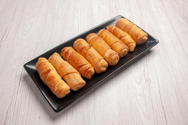 Zijaanzicht buisvormig gebaksbord van buisvormig gebak op de zwarte plaat op de witte tafel