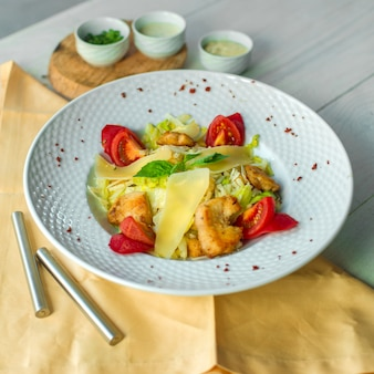 Zijaanzicht caesar salade met kip en sauzen