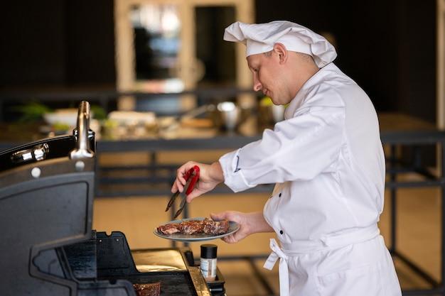 Zijaanzicht chef-kok koken in de keuken
