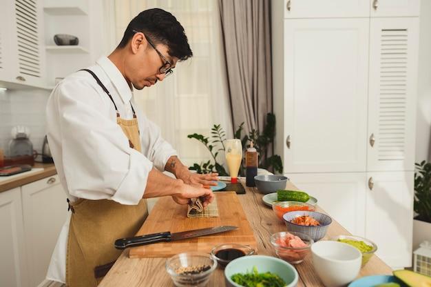 Zijaanzicht chef op een keuken rollende sushi op een bamboe mat promo voor restaurant