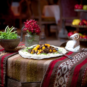 Zijaanzicht cizbiz met verse groenten en beeldjes van ram in lavash
